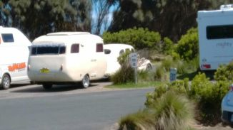A cute retro van and car complete with lace curtains on the back window